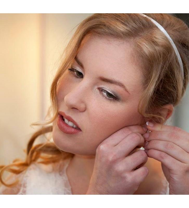 Mooie bruid doet oorbel in.
